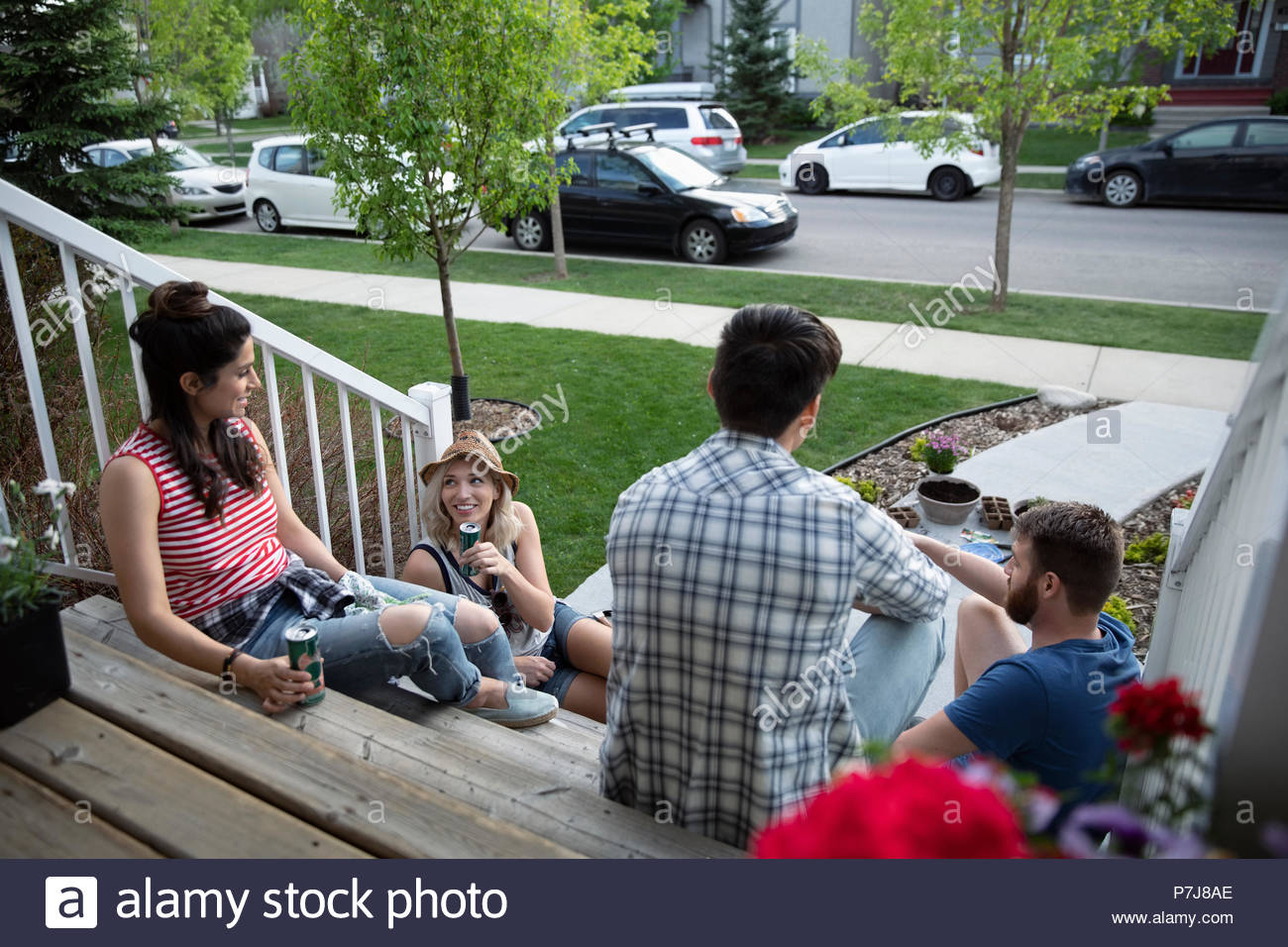 Couples taking a break from gardening, relaxing on front stoop - Stock Image