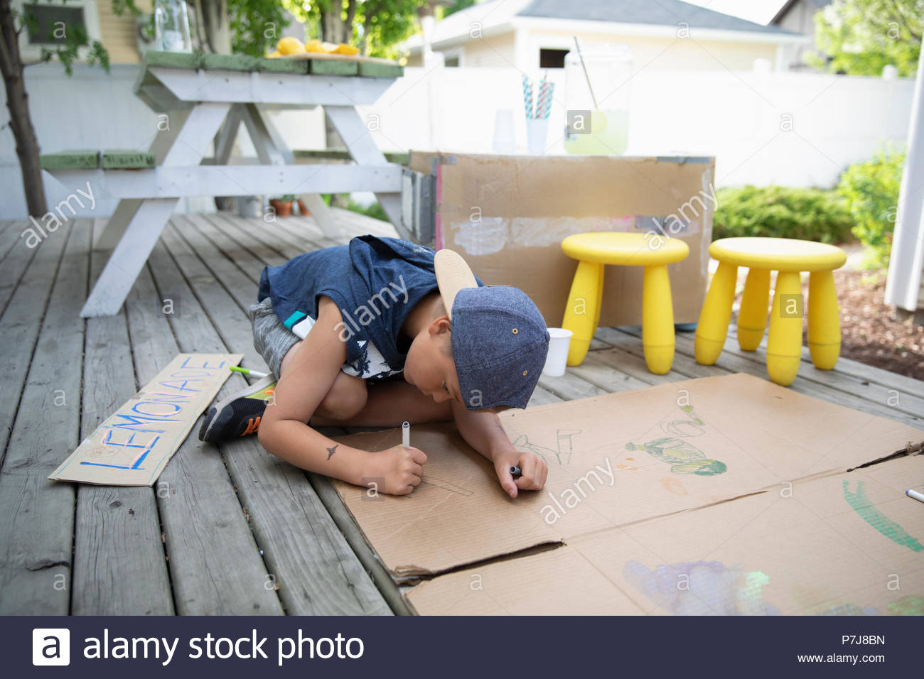 Boy drawing on cardboard, making lemonade stand - Stock Image
