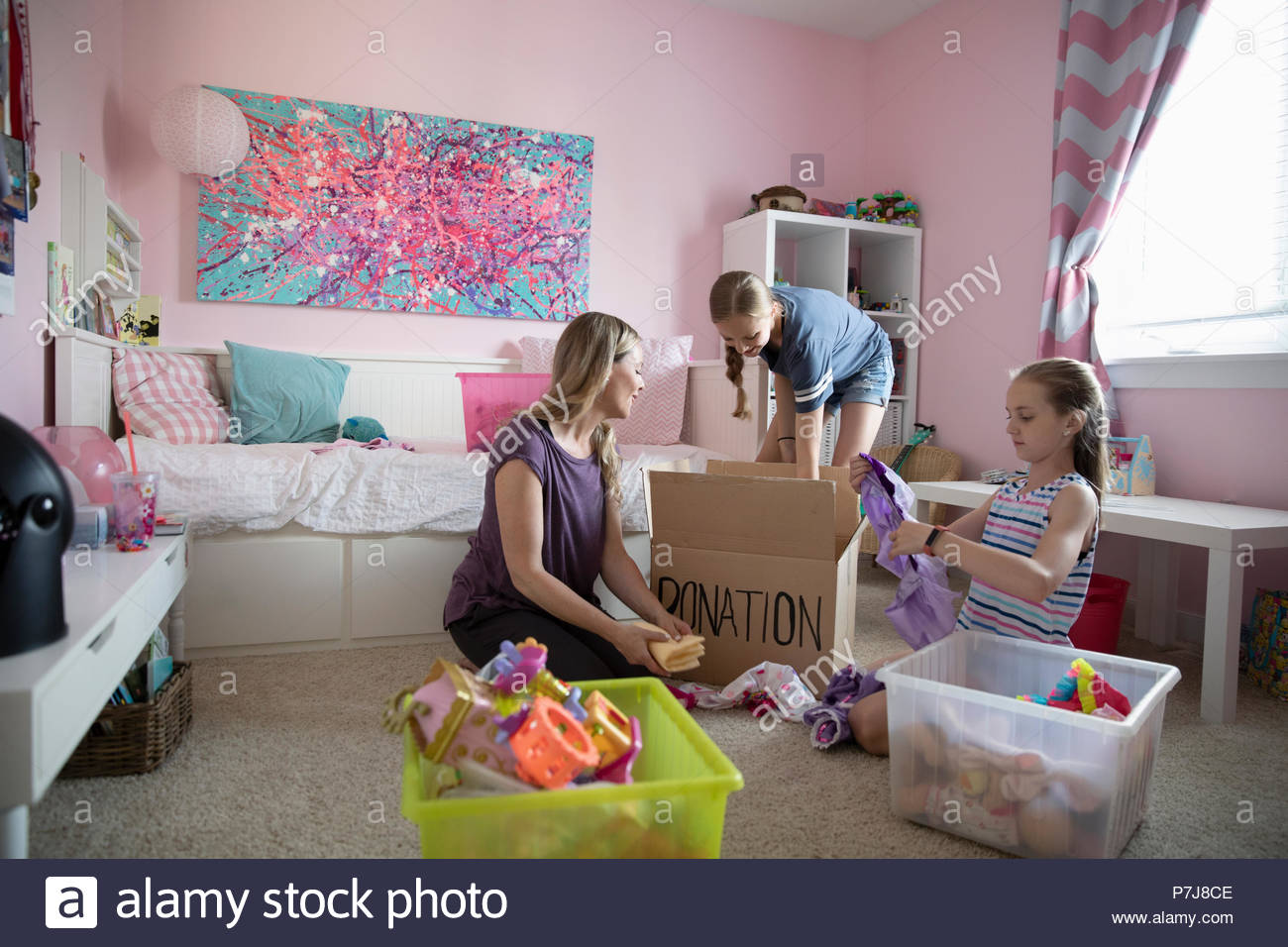 Mother and daughters organizing bedroom, donating - Stock Image