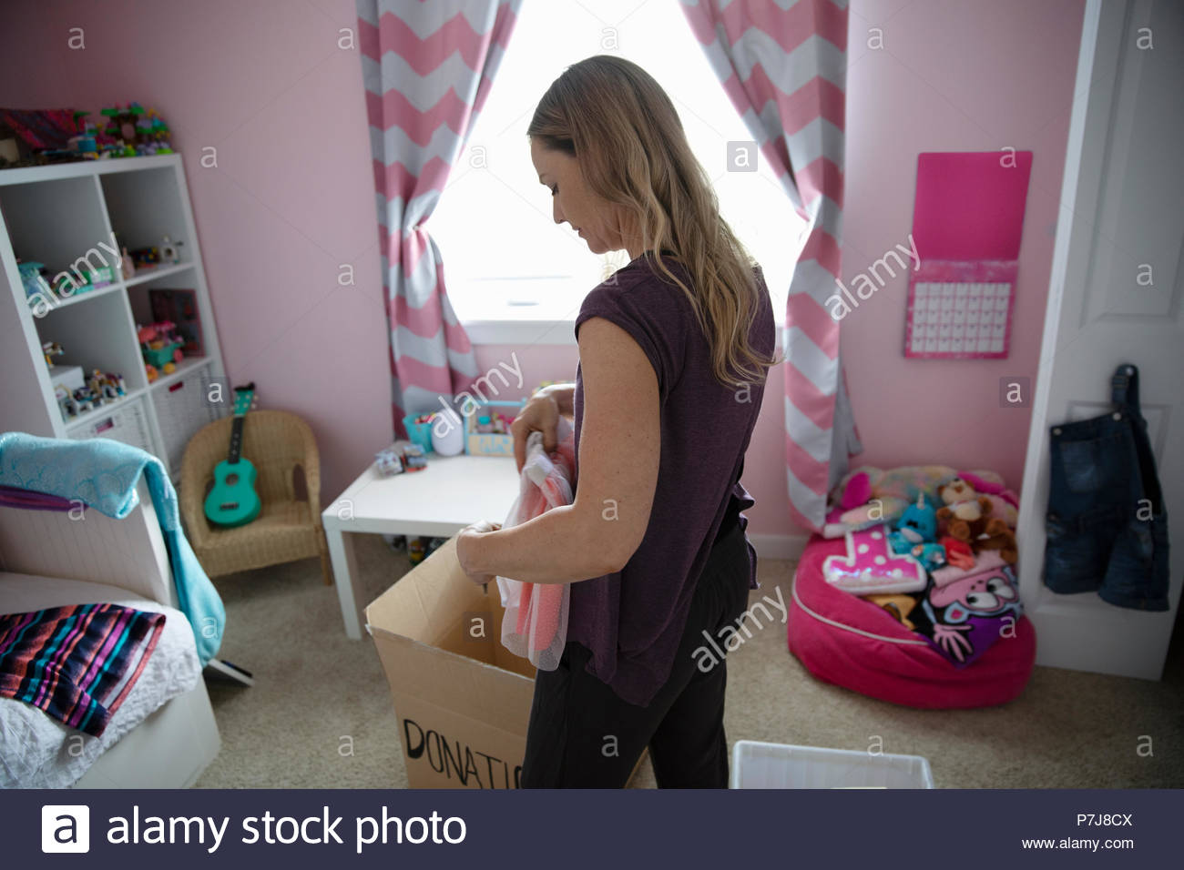 Mother organizing daughters bedroom, donating clothes - Stock Image