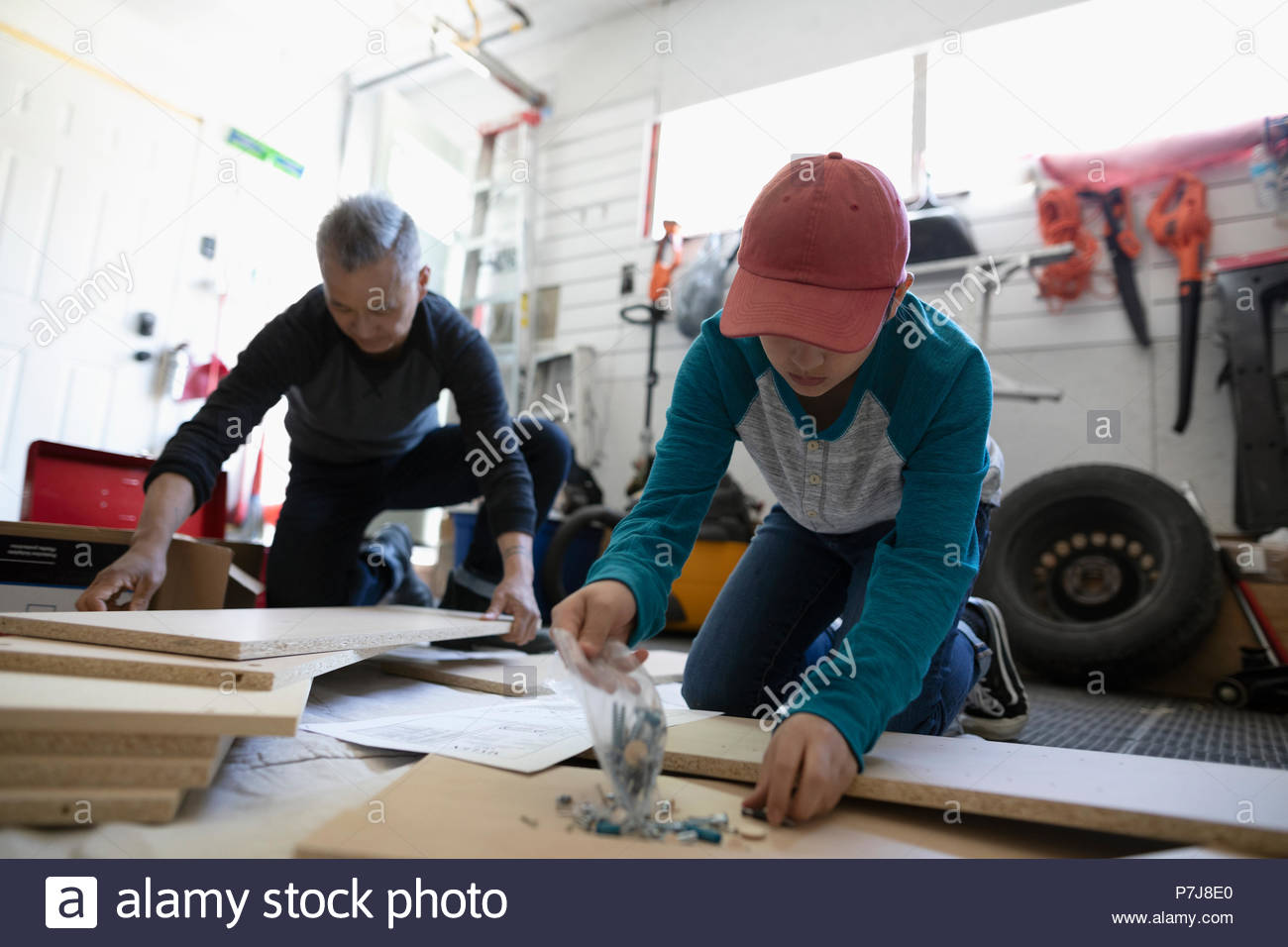 Father and son assembling flat pack furniture in garage - Stock Image