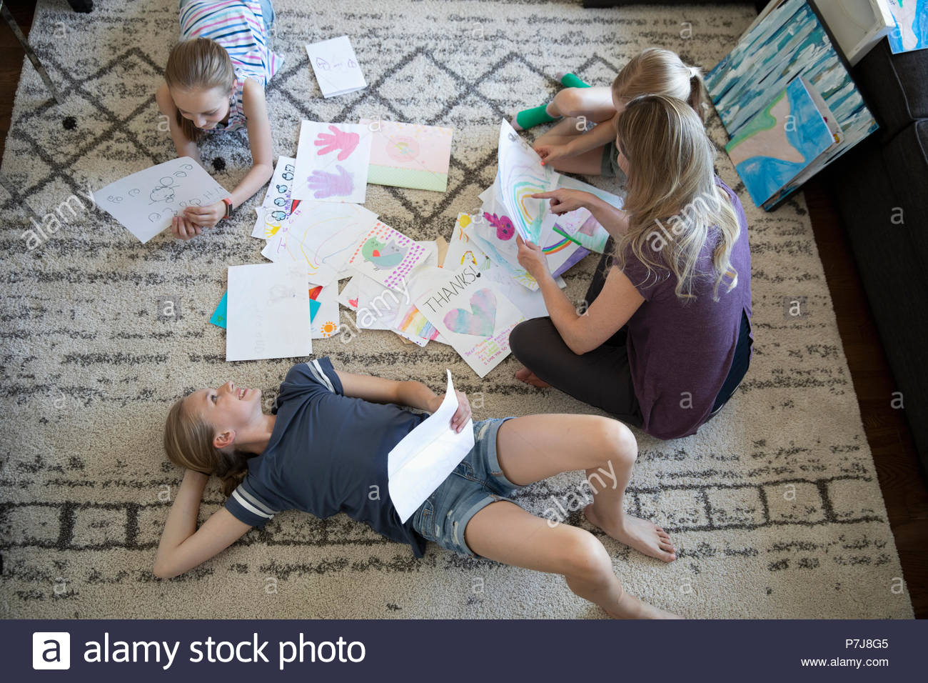Mother and daughters looking at drawings on living room floor - Stock Image