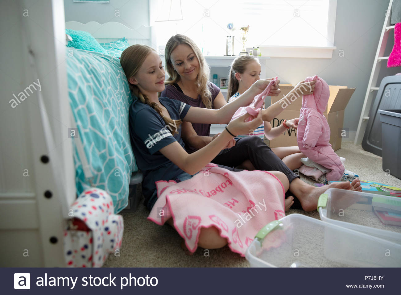 Mother and daughters donating baby clothes in bedroom - Stock Image