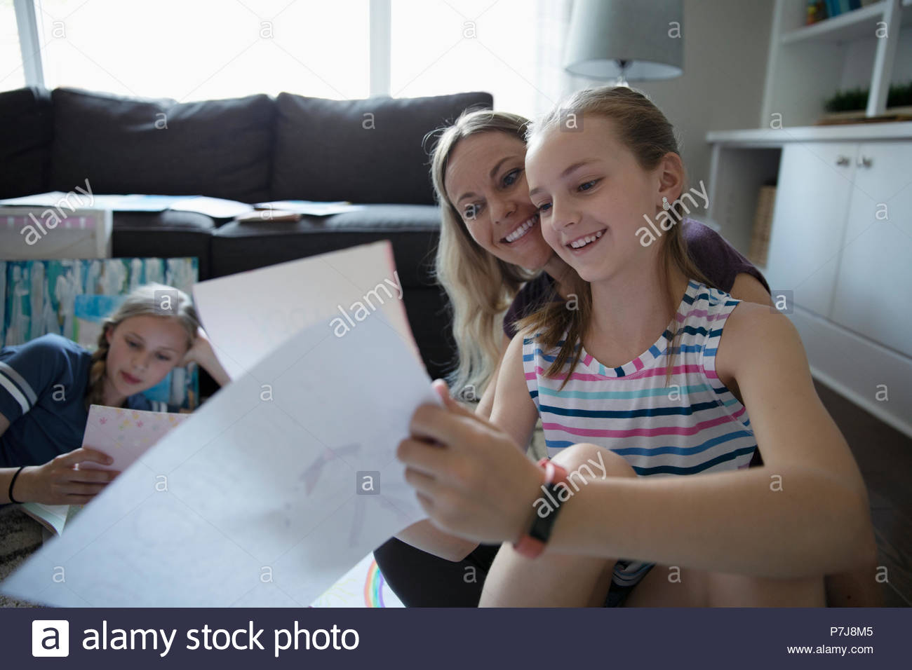 Daughter showing drawings to mother - Stock Image