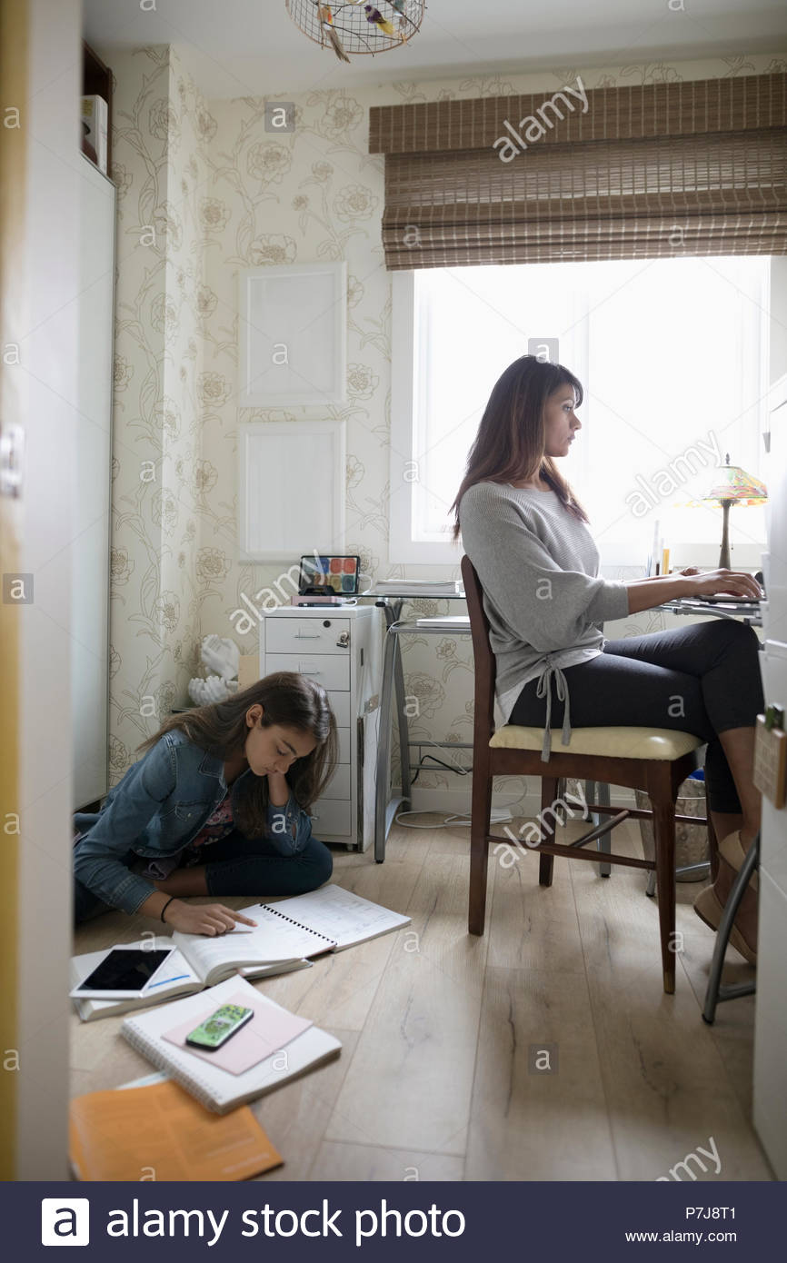 Tween daughter studying on floor behind mother working in home office - Stock Image
