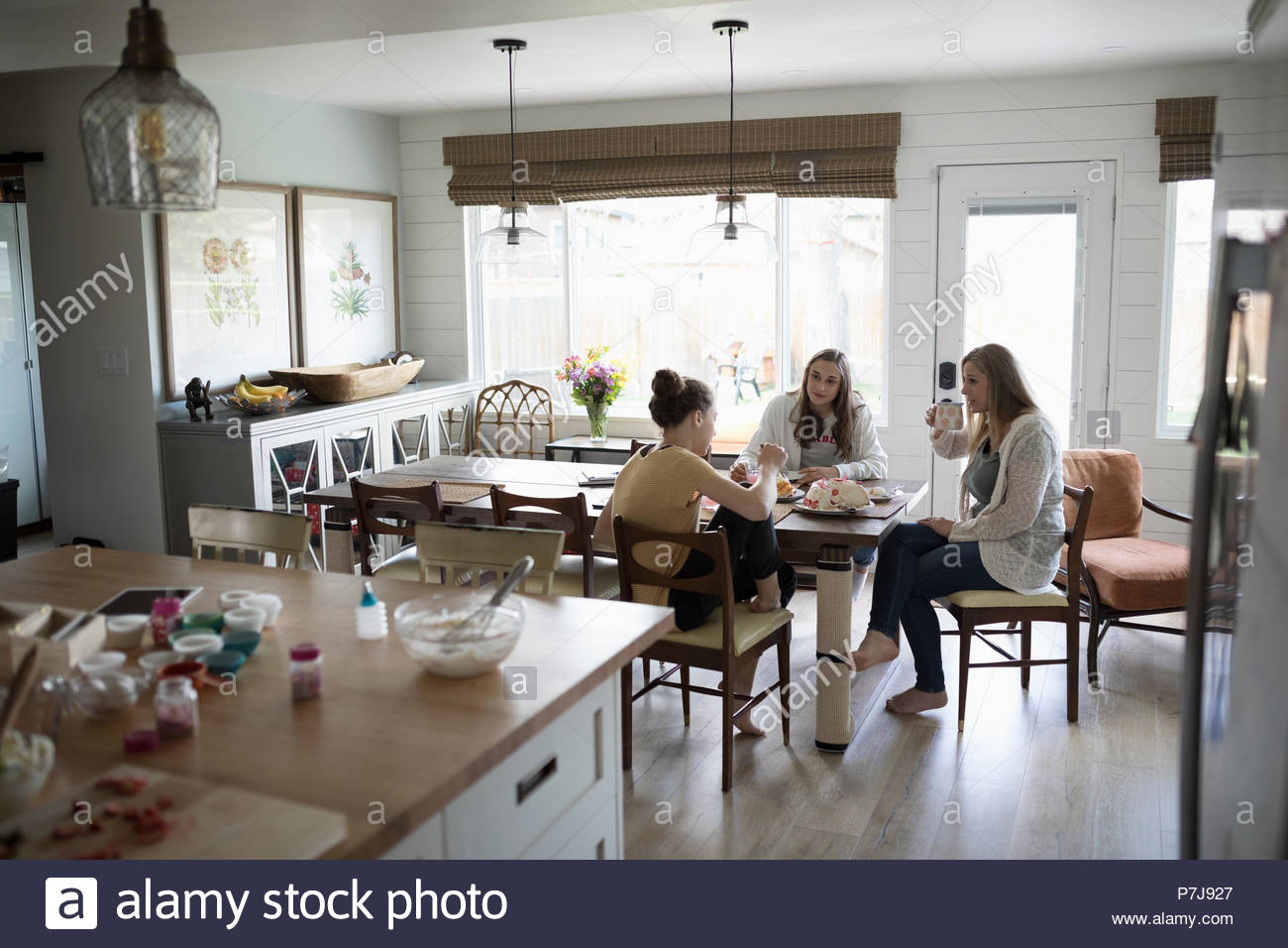 Mother and teenage daughters enjoying birthday cake at table - Stock Image