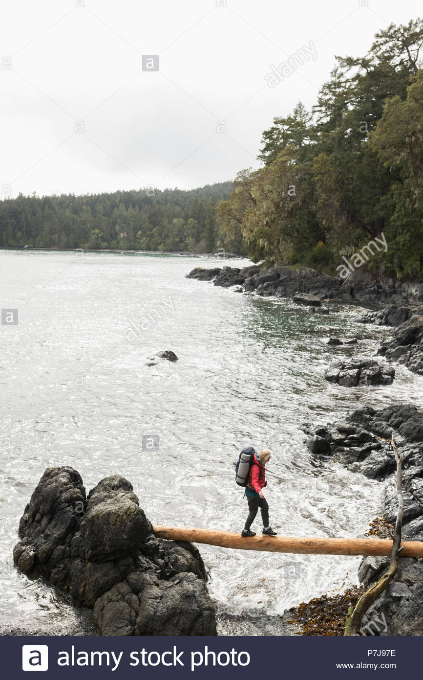 Woman backpacking, crossing fallen log between rocks over ocean - Stock Image