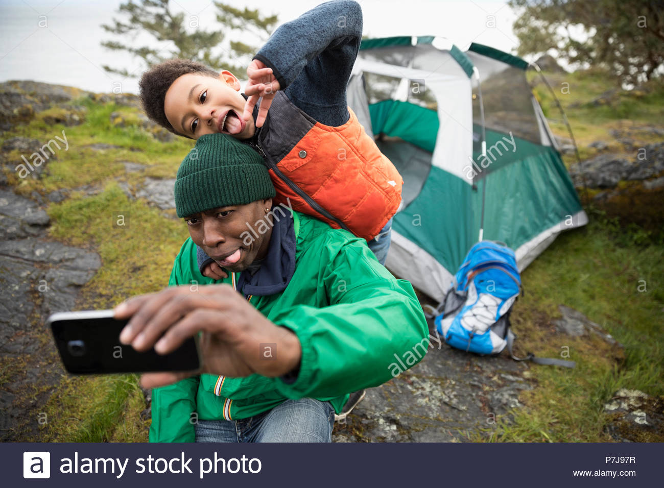 Playful father and son making faces, taking selfie at campsite - Stock Image
