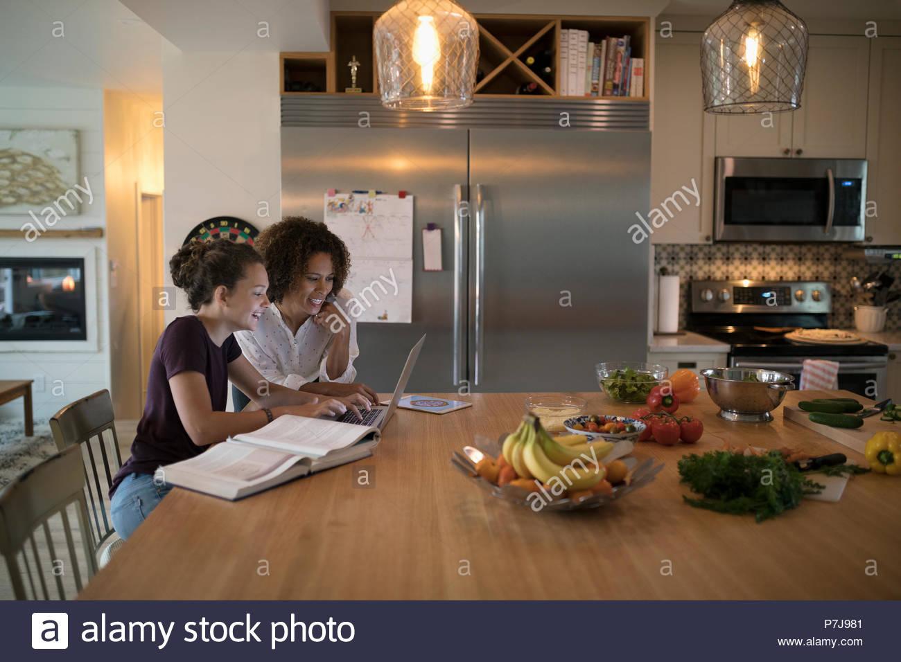 Mother helping tween daughter doing homework at laptop in kitchen - Stock Image