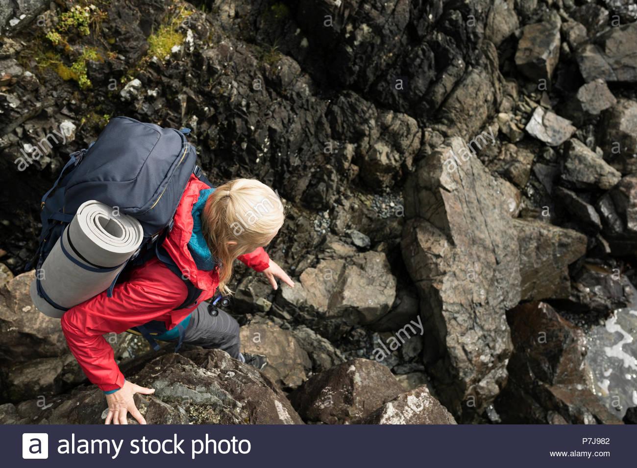 Active senior woman backpacking, descending craggy rocks - Stock Image