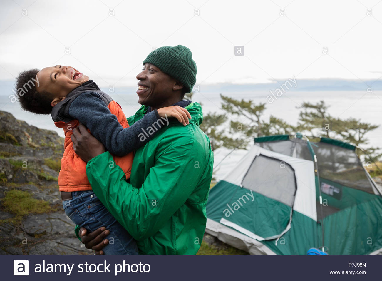 Playful father and son camping - Stock Image