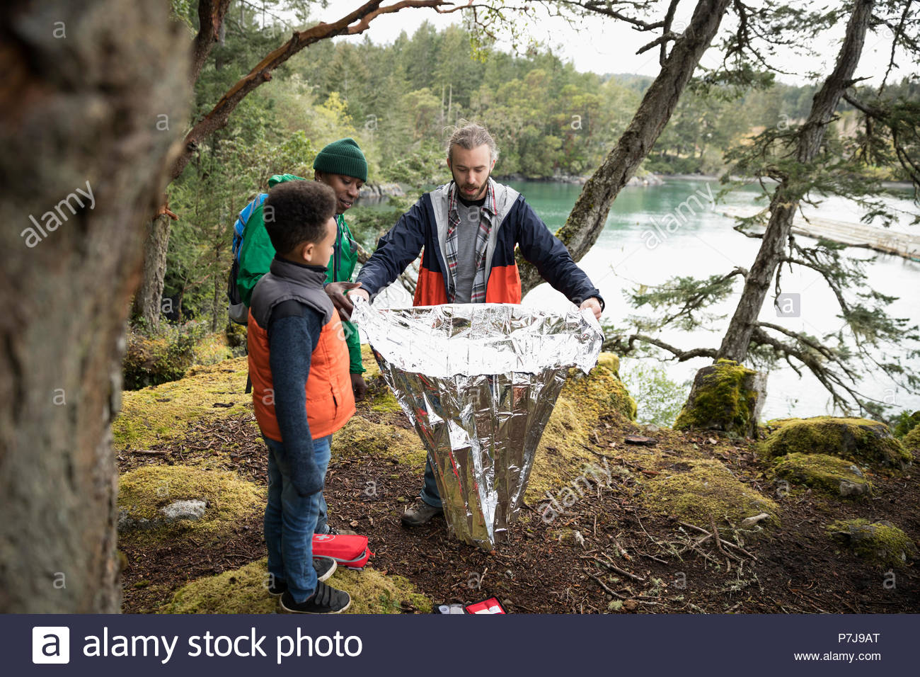 Trail guide showing thermal blanket to father and son in woods - Stock Image