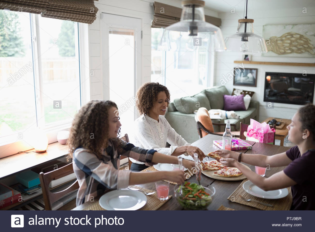 Mother and daughters enjoying Mothers Day pizza lunch - Stock Image