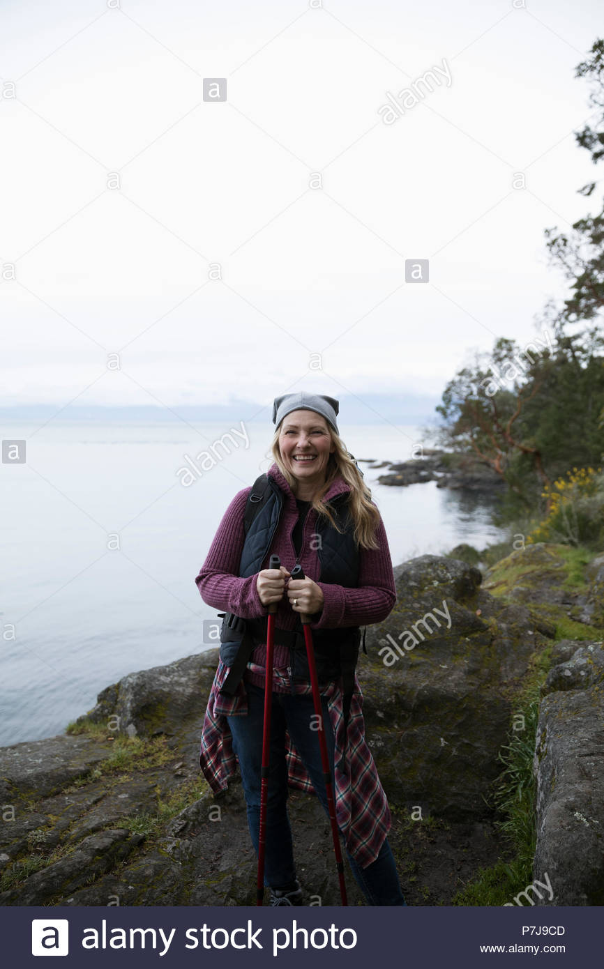 Portrait smiling, carefree woman backpacking along ocean - Stock Image
