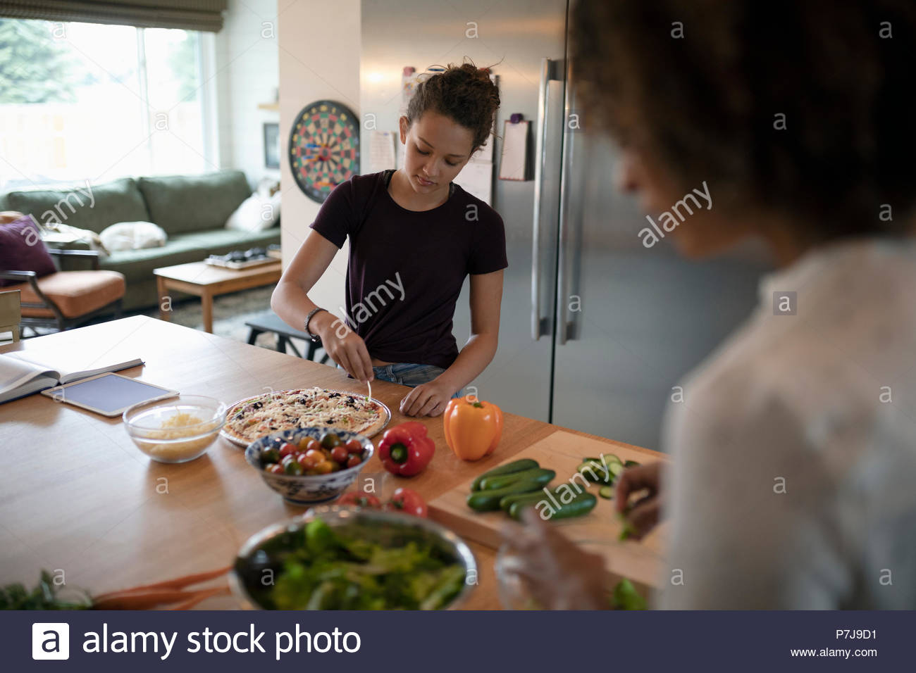Mother and daughter cooking, preparing vegetables and pizza in kitchen - Stock Image