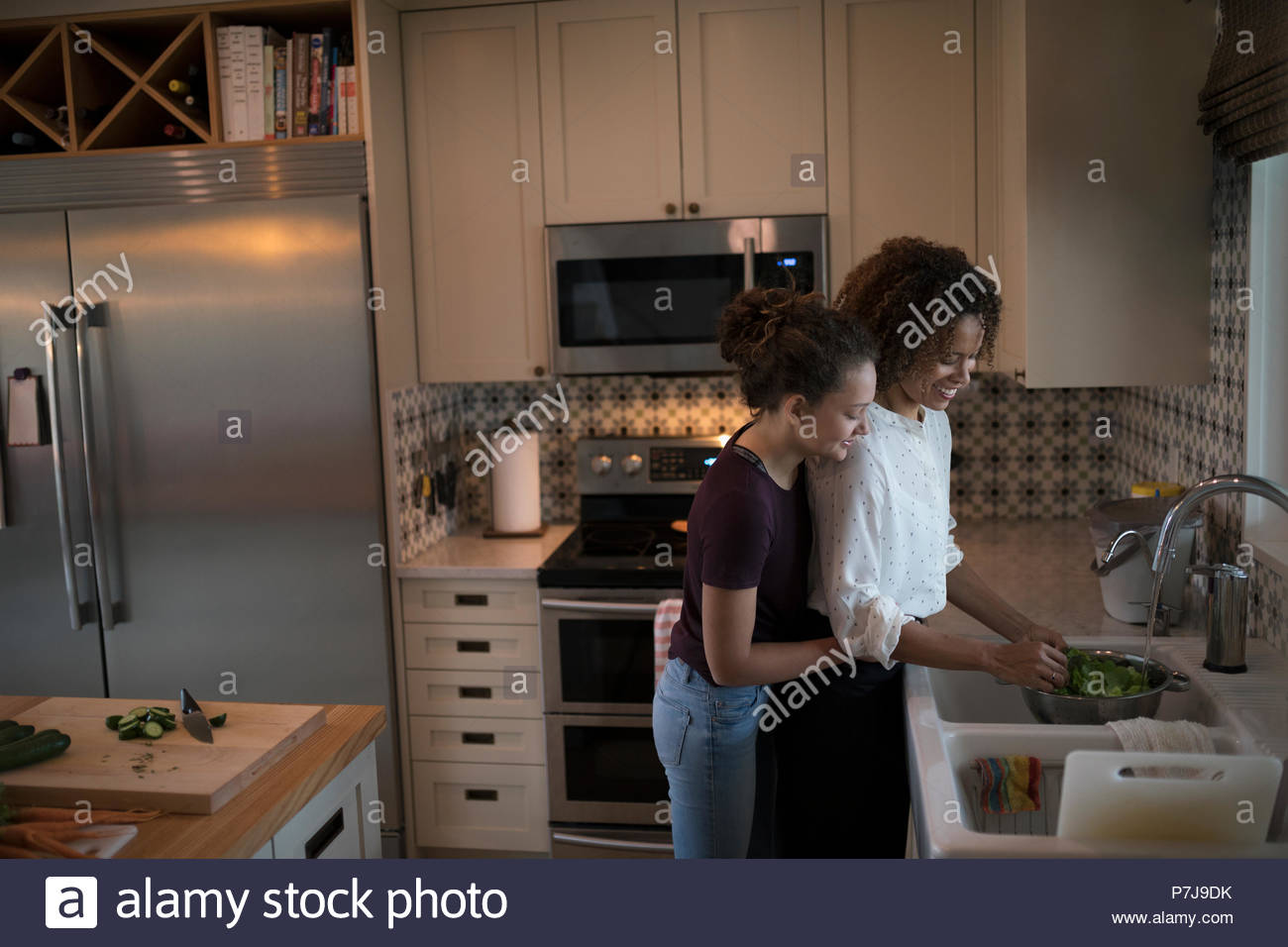 Affectionate mother and daughter washing vegetables at kitchen sink - Stock Image