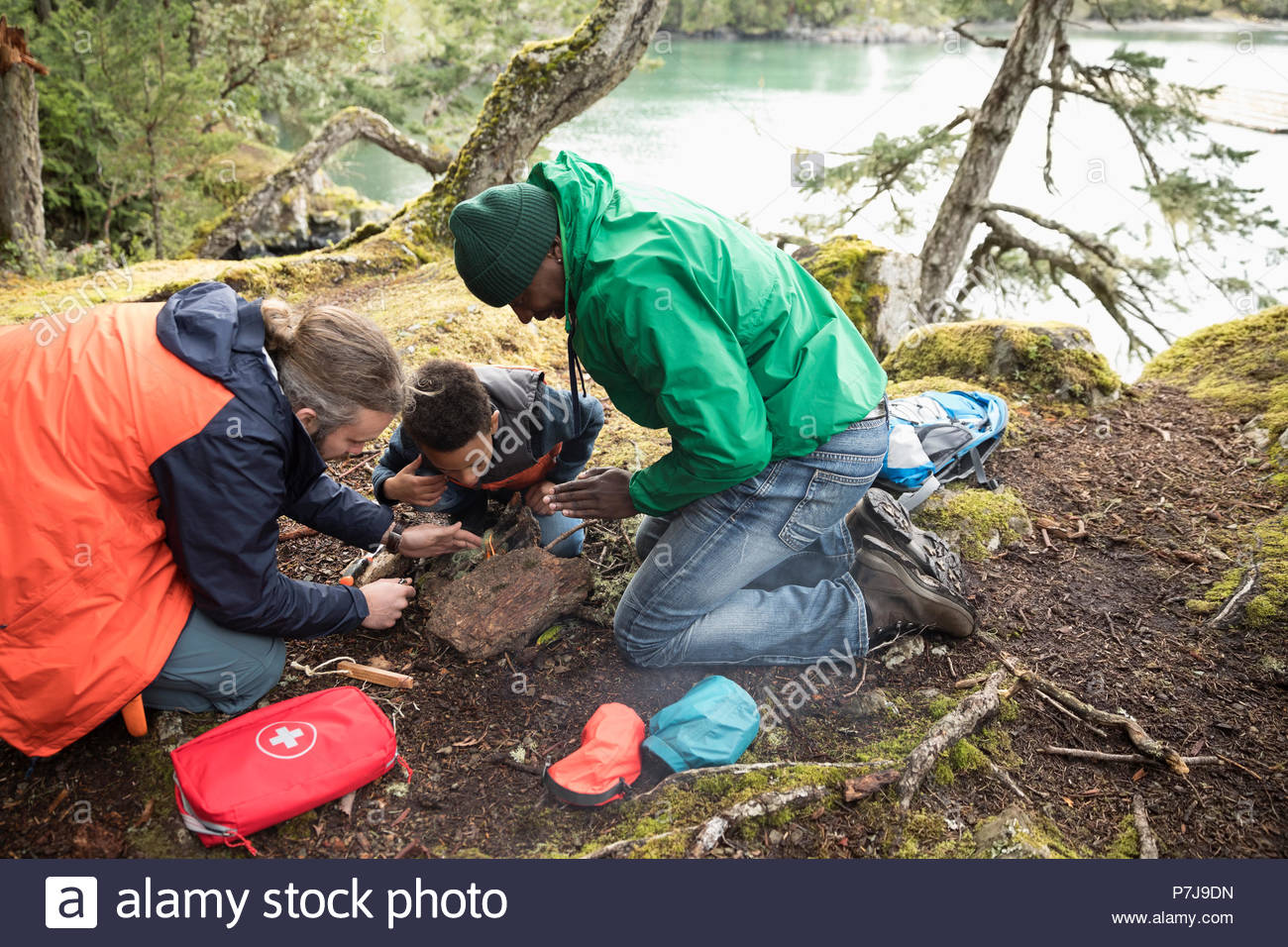 Trail guide teaching father and son how to build a campfire in woods - Stock Image