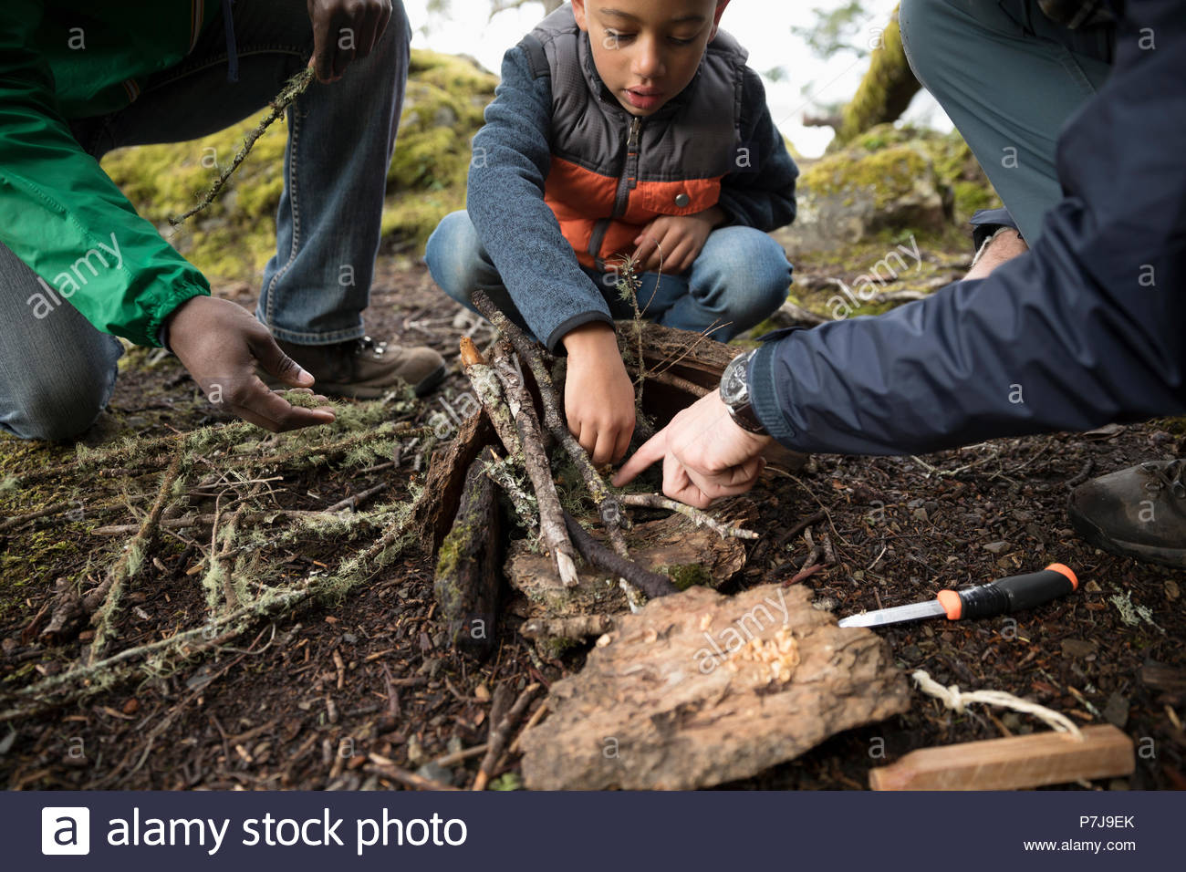 Trail guide and father helping boy build a fire in woods - Stock Image