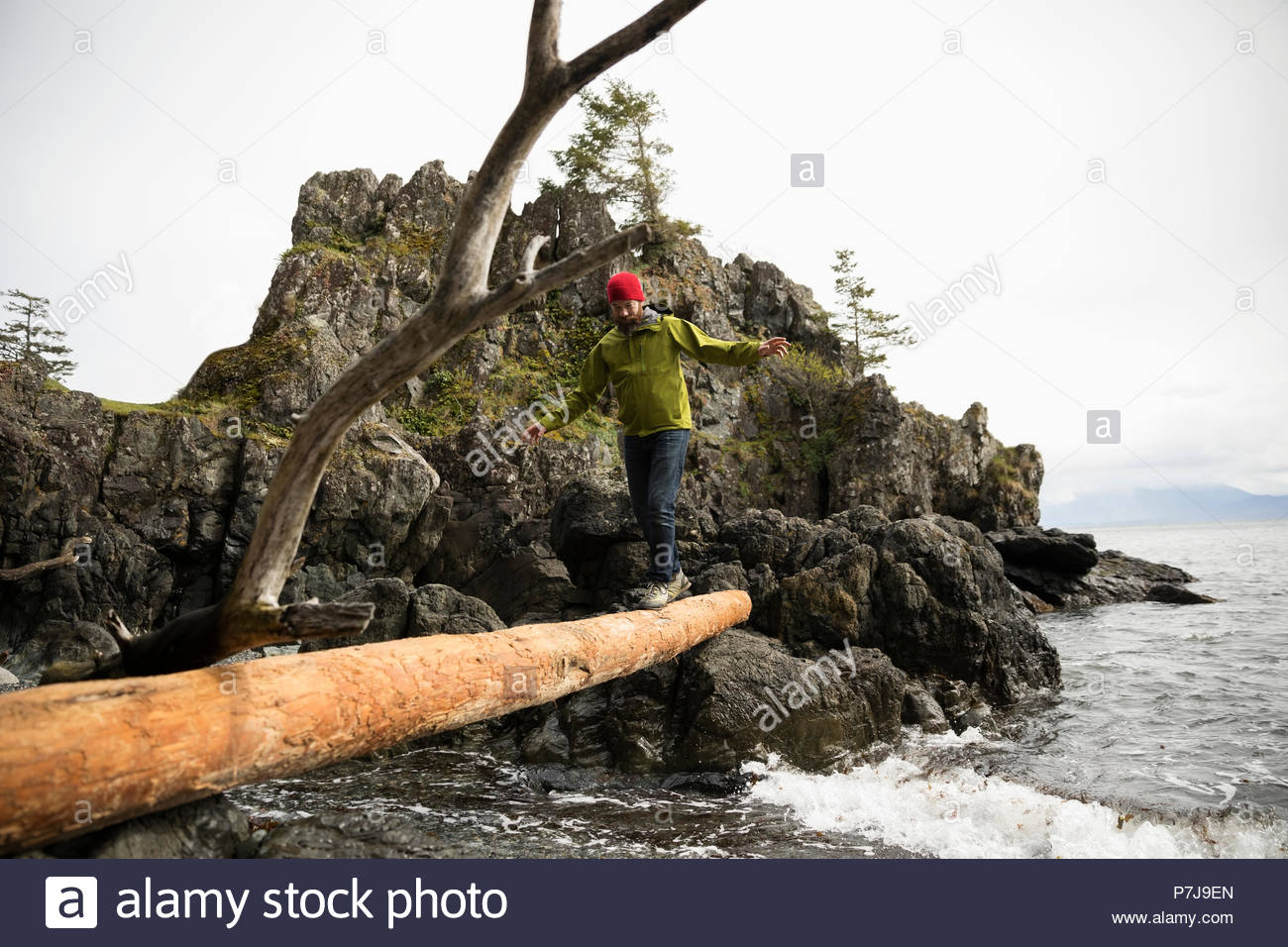 Male backpacker crossing fallen log over ocean - Stock Image