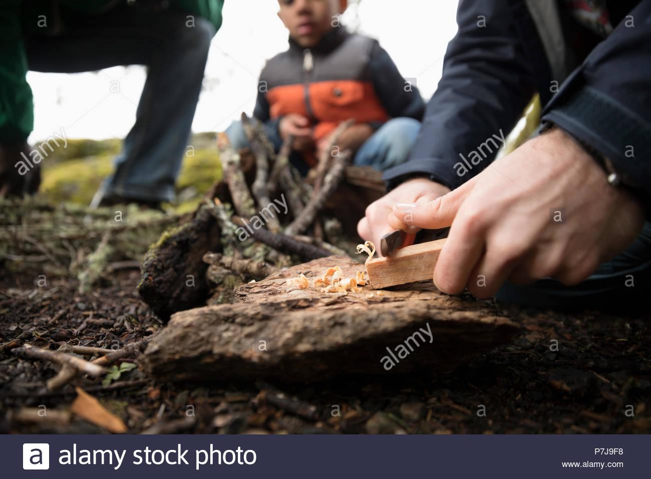 Man preparing campfire in woods - Stock Image