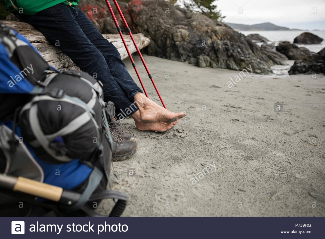 Barefoot man backpacking, resting on rugged beach Stock Photo