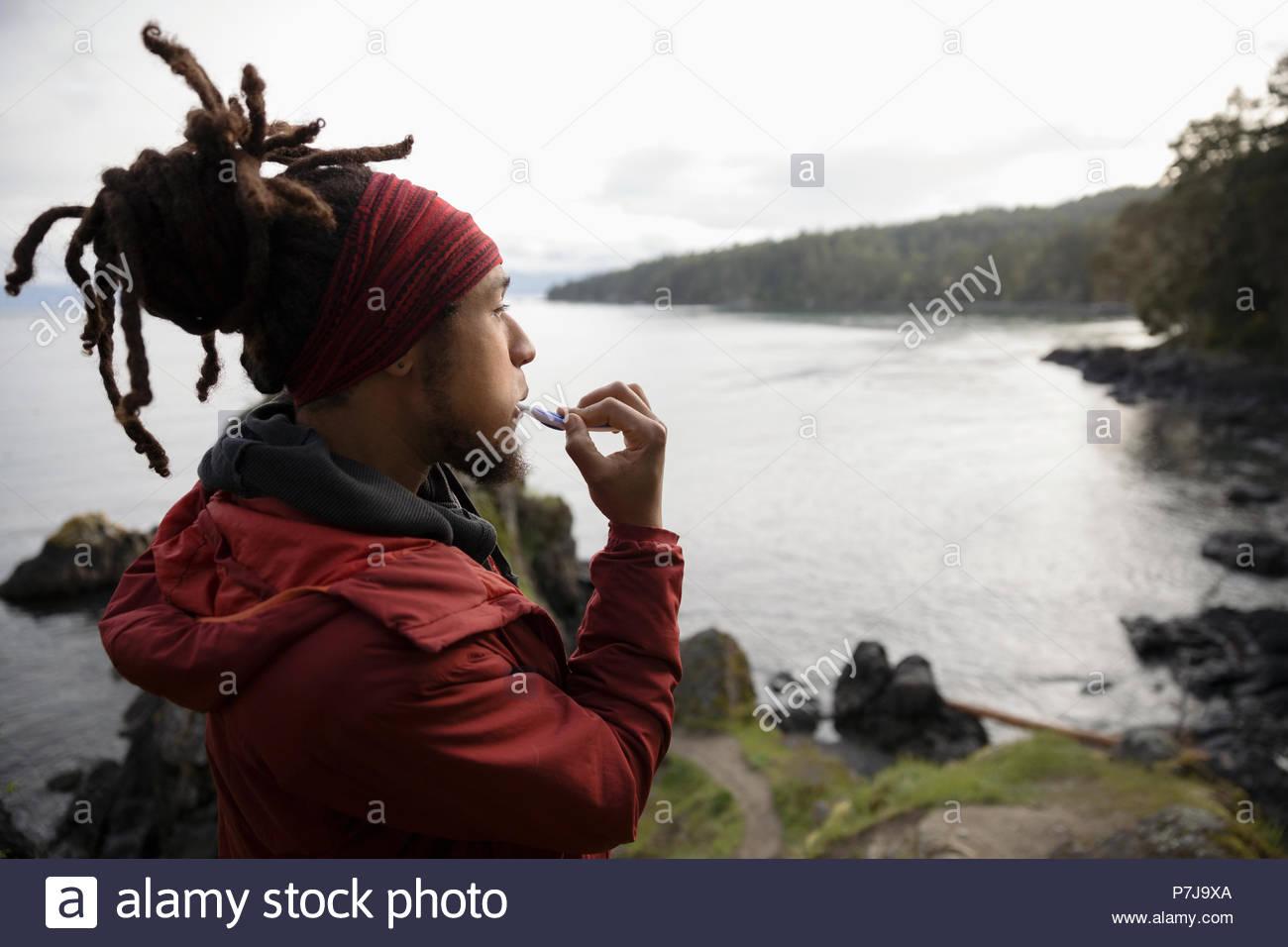 Male backpacker brushing teeth on cliff overlooking ocean - Stock Image
