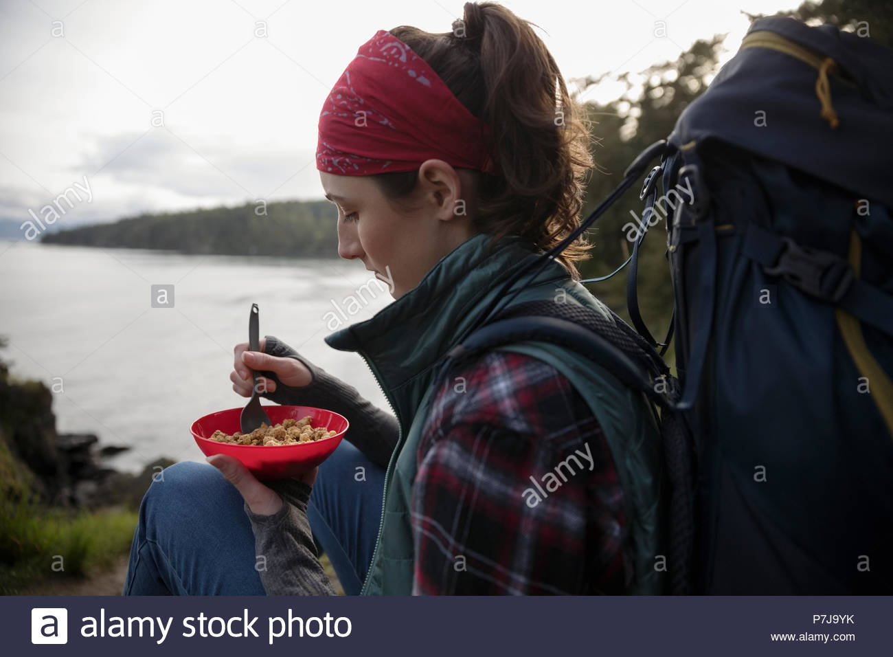 Female backpacker eating cereal on cliff overlooking ocean - Stock Image