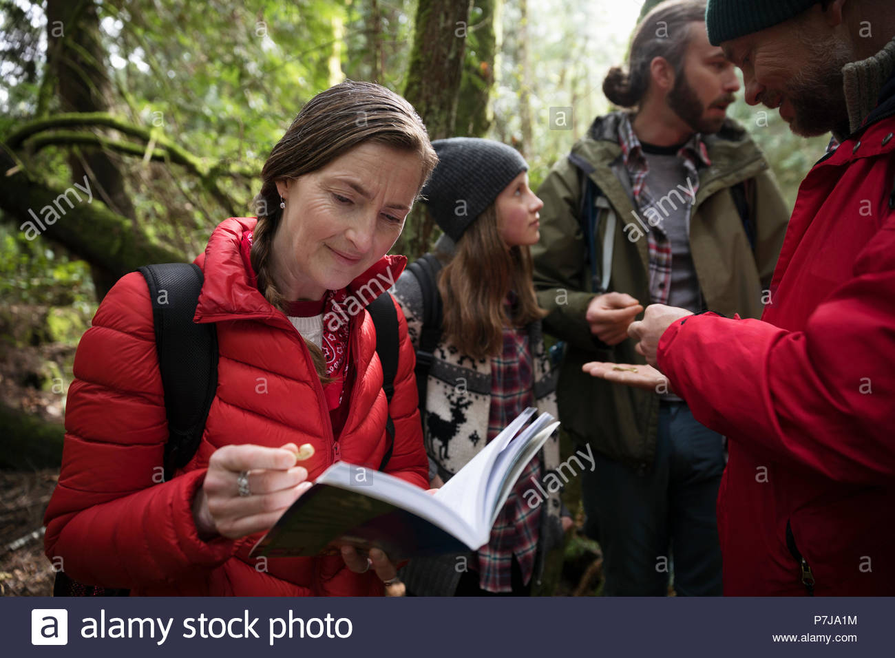 Trail guide and family hiking, exploring in woods - Stock Image