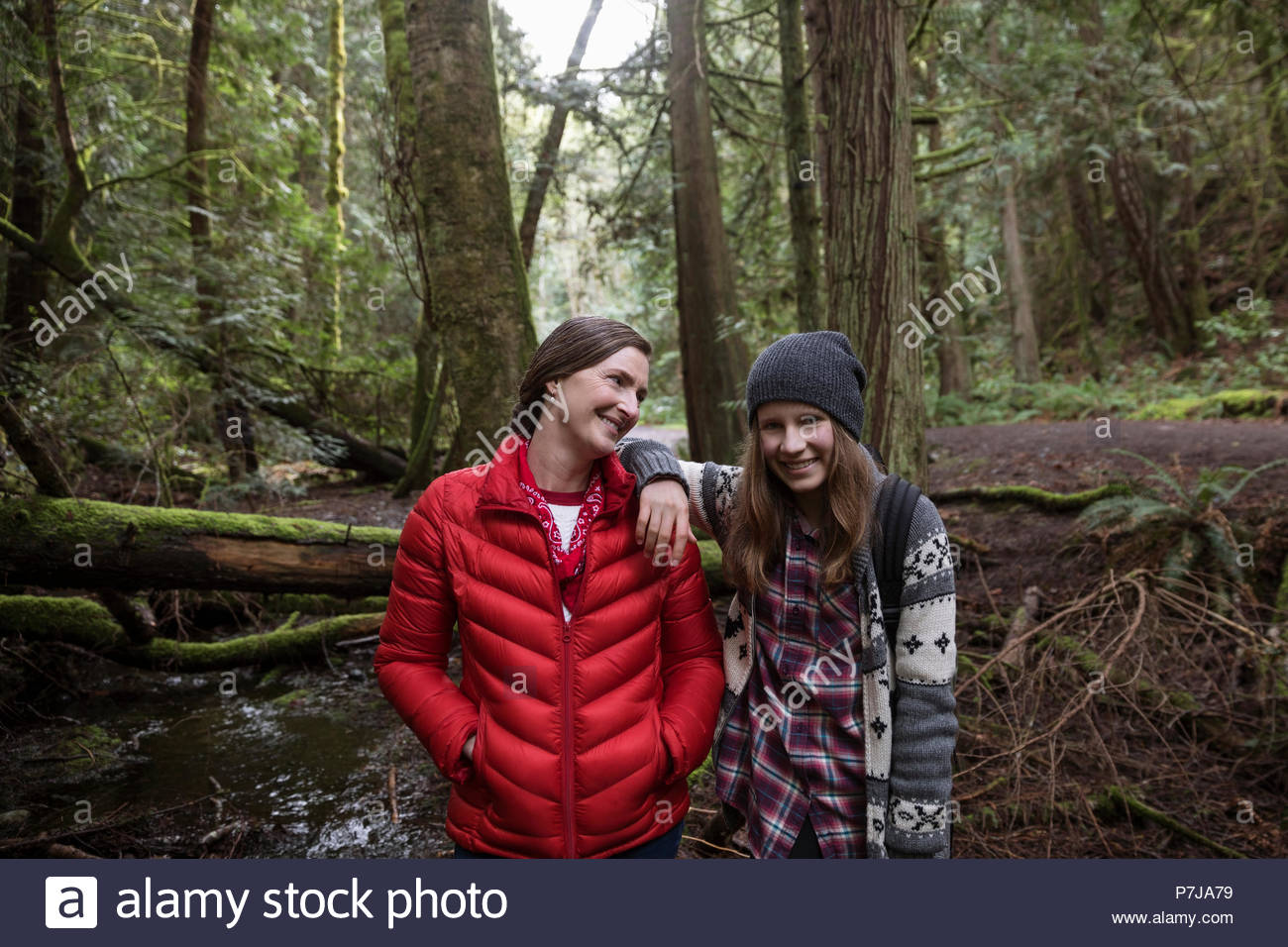 Portrait confident mother and daughter hiking in woods - Stock Image