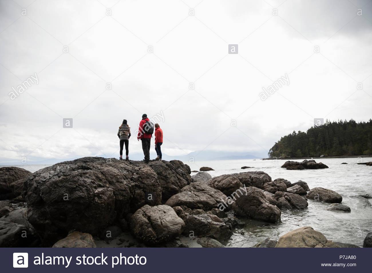 Family on rocks enjoying rugged ocean view - Stock Image