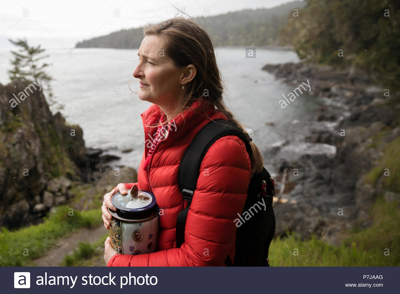 Woman with urn spreading ashes on cliff overlooking ocean - Stock Image