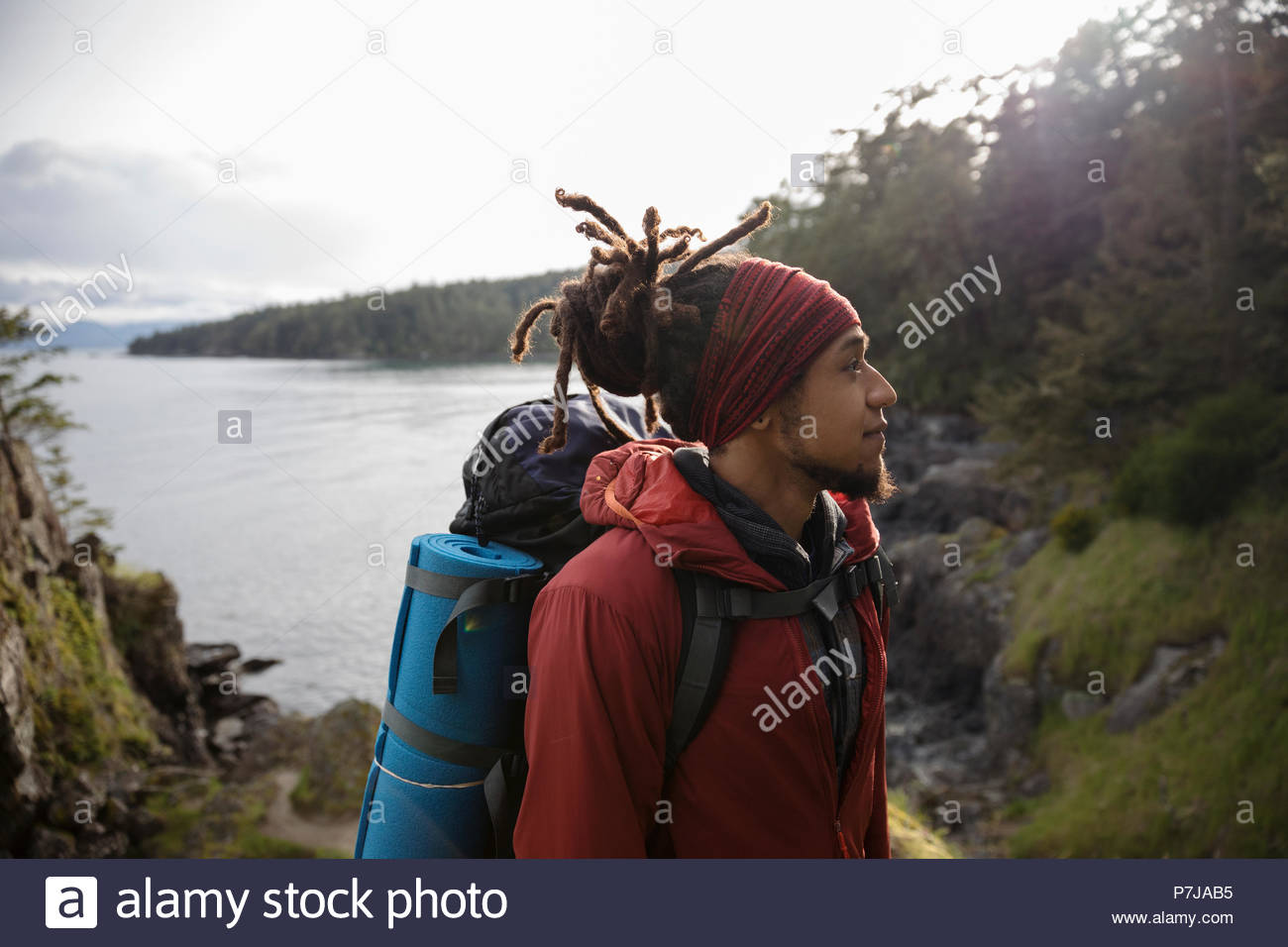 Thoughtful male backpacker hiking along ocean - Stock Image