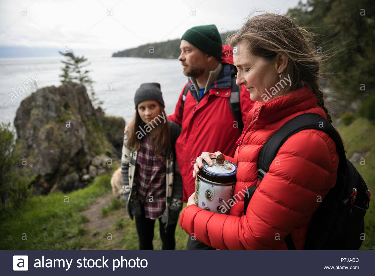 Family with urn spreading ashes on cliff overlooking ocean - Stock Image
