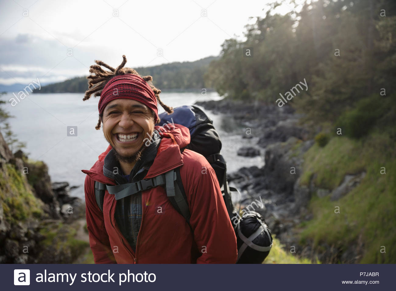 Portrait happy, enthusiastic male backpacker hiking along ocean - Stock Image
