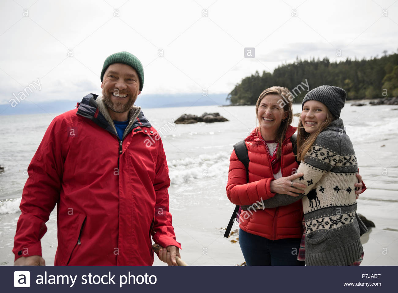 Happy family on rugged beach - Stock Image
