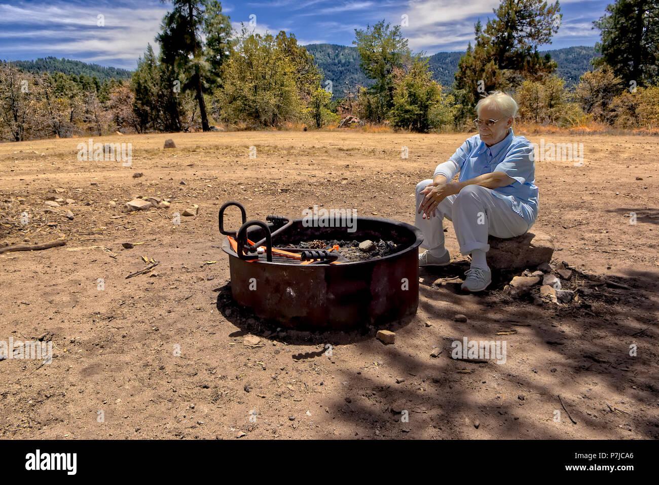 Senior woman sitting by a fire pit during fire ban, Prescott, Arizona, America, USA - Stock Image