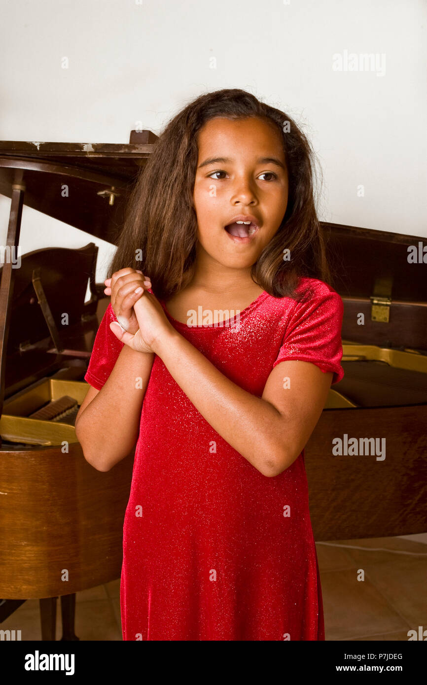 Young African American girl happily singing at her recital. MR © Myrleen Pearson - Stock Image