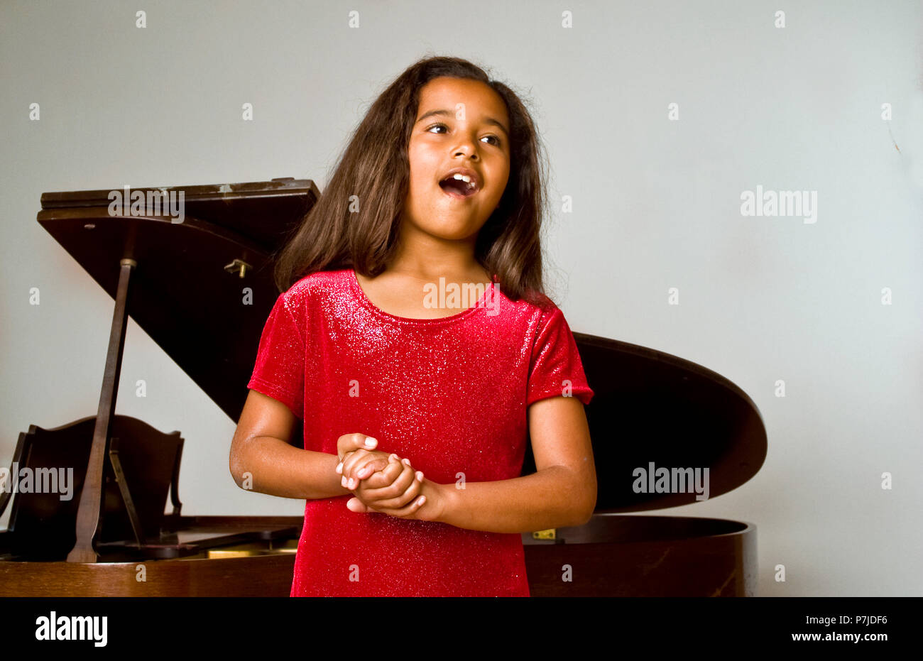 Young African American girl singing at her recital. MR © Myrleen Pearson - Stock Image