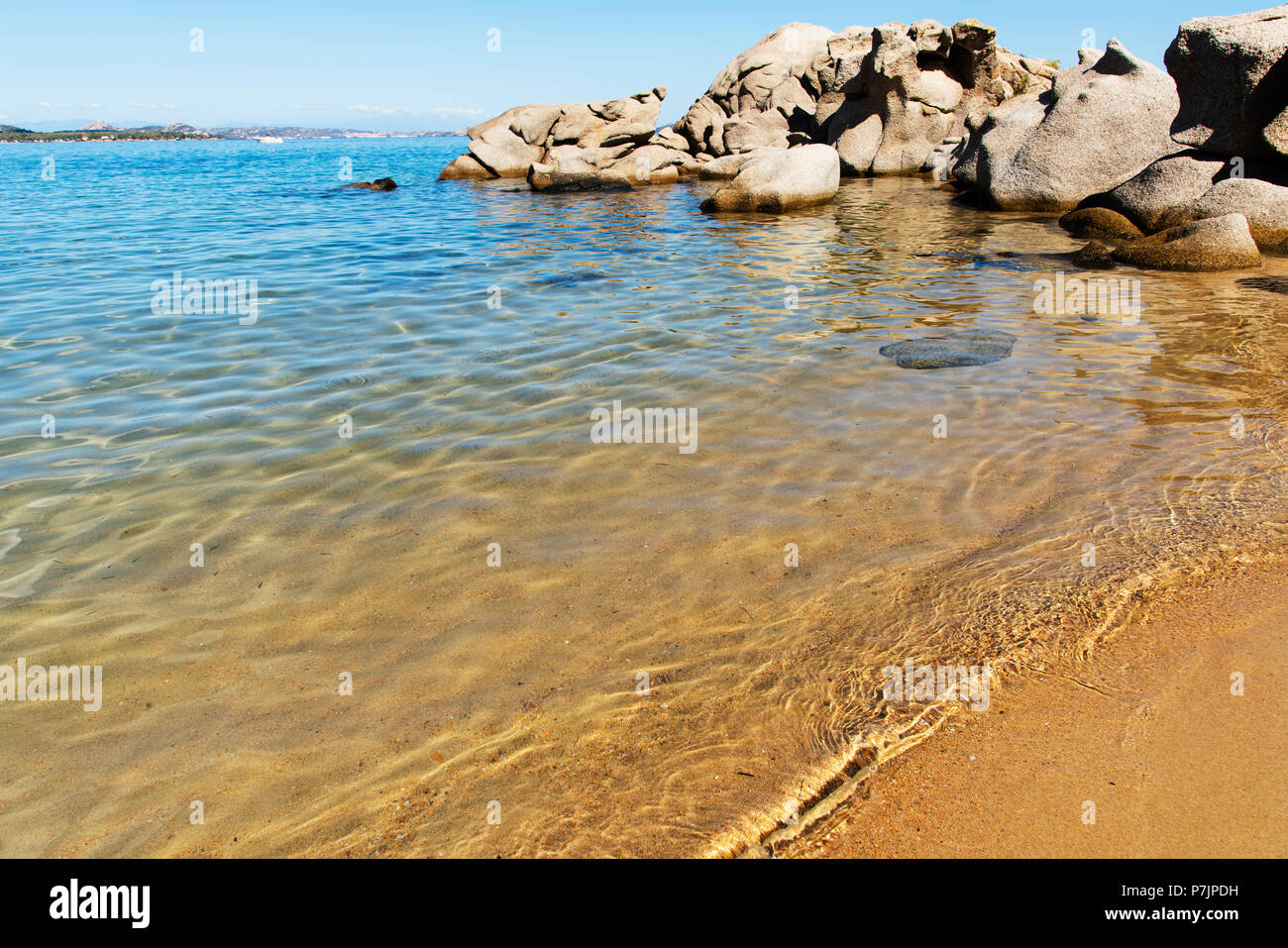 a view of the clear water of the Mediterranean sea and the peculiar rock formations in Cala Ginepro beach, in the famous Costa Smeralda, Sardinia, Ita - Stock Image