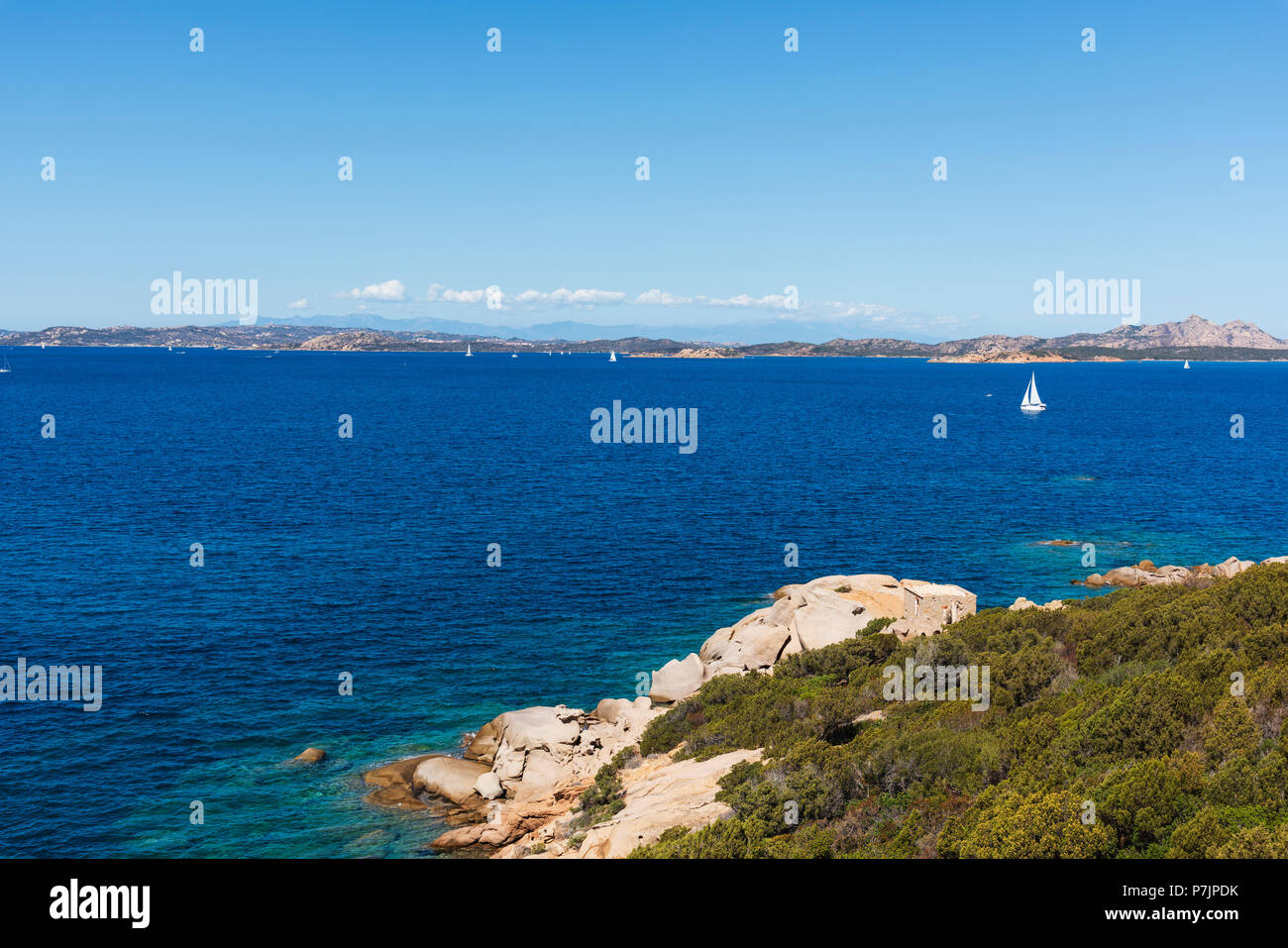 a view of the clear water of the Mediterranean sea and a group of rock formations in a quiet beach in the coast of Baja Sardinia, in the famous Costa  - Stock Image