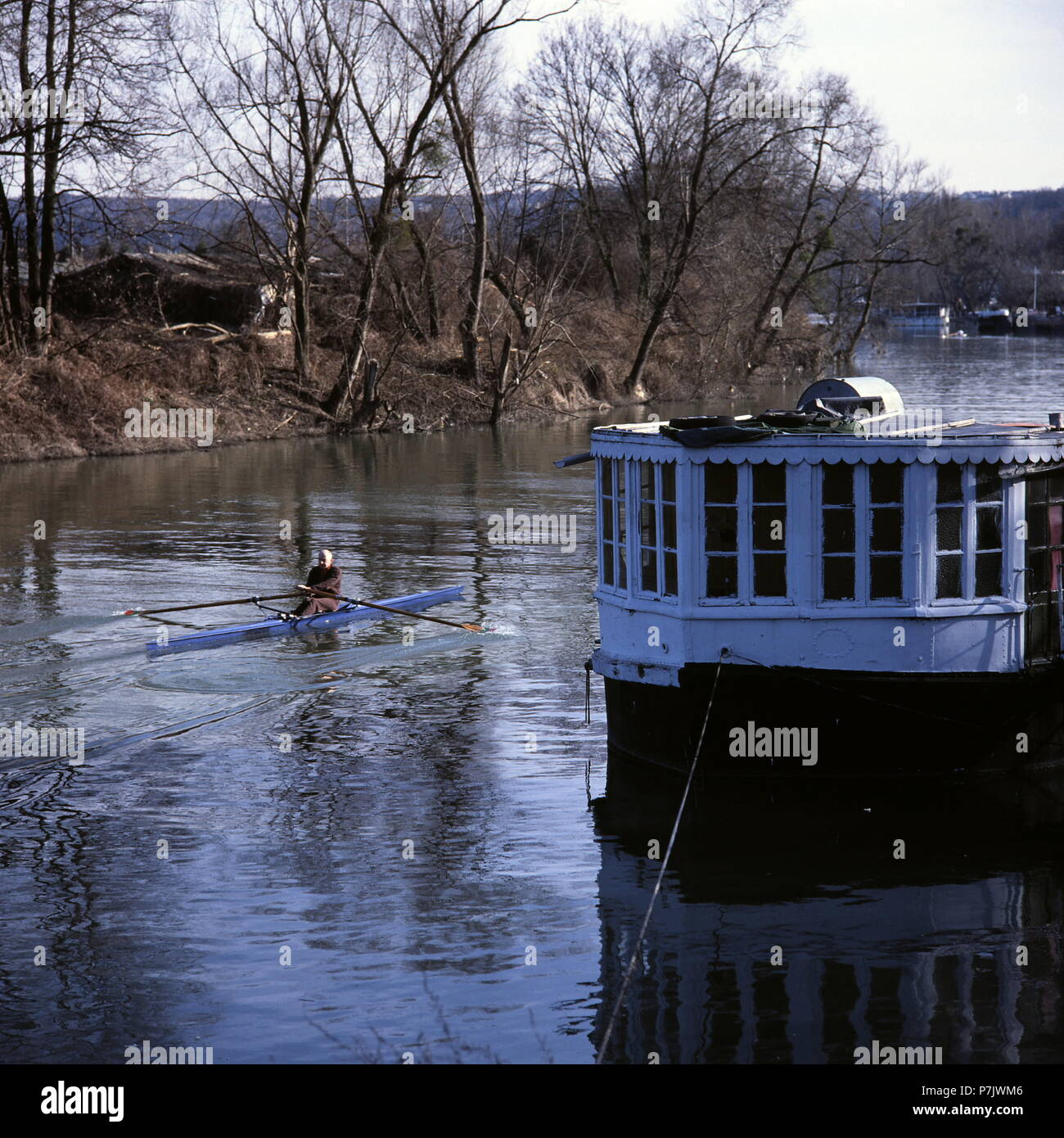 AJAXNETPHOTO. LE PORT MARLY, FRANCE. - RIVER SEINE - A ONE-MAN SCULL HEADS UPSTREAM PAST OLD HOUSEBOATS MOORED ON THE RIVERSIDE. 19TH CENTURY IMPRESSIONIST ARTISTS ALFRED SISLEY AND CAMILLE PISSARRO BOTH MADE STUDIES OF RIVER LIFE NEAR HERE. PHOTO:JONATHAN EASTLAND/AJAX REF:50 - Stock Image