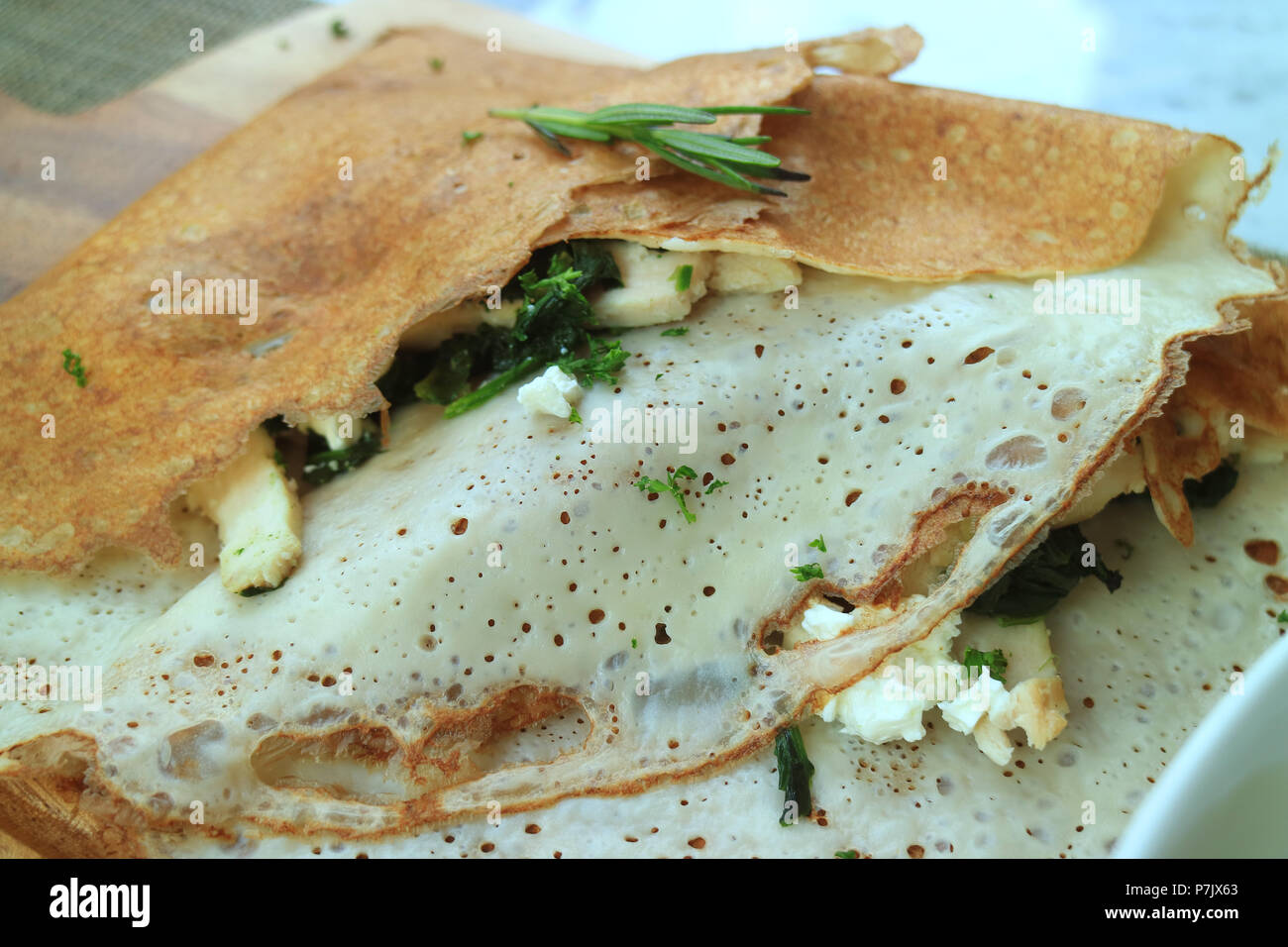 Close up of classic French savory crepe stuffed with spinach, chicken and cheese - Stock Image