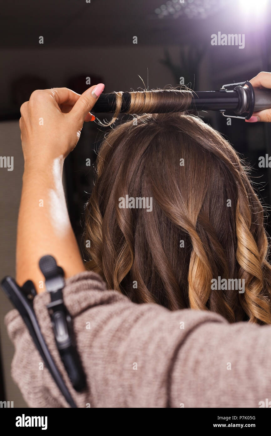 hairdresser making a hair curling to a client - Stock Image