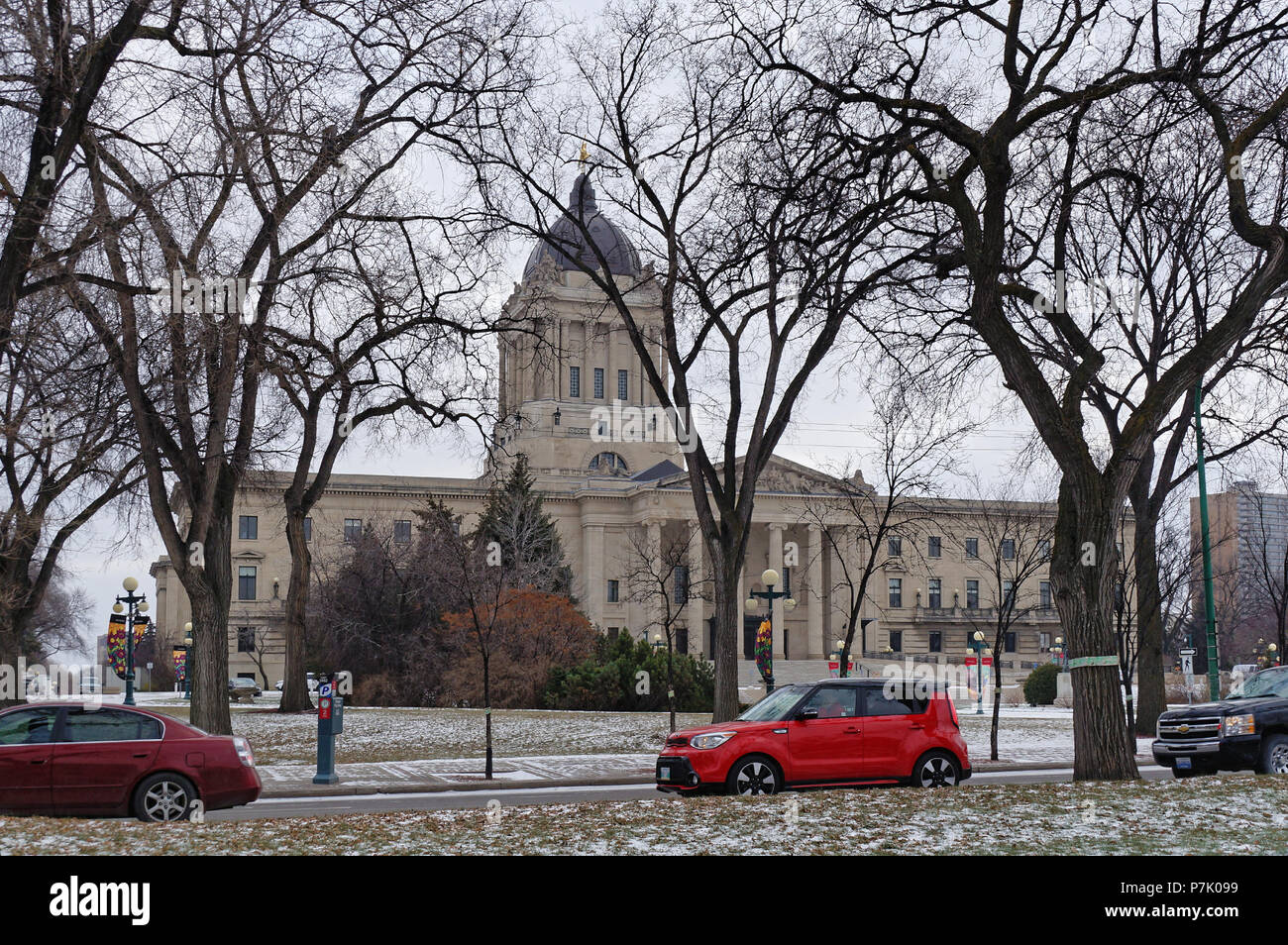 WINNIPEG, CANADA - 2014-11-16: Cars on winter Memorial Boulevard in front of Manitoba Legislature building. This neoclassical structure built in 1920 in the centre of Winnipeg stands 77 metres tall - Stock Image