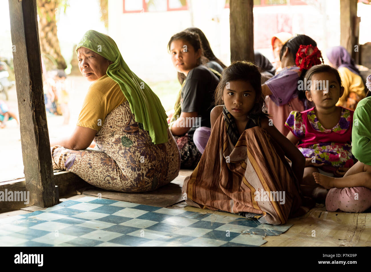 Young girl and other children and women in the port city of Singkil, Indonesia, Stock Photo