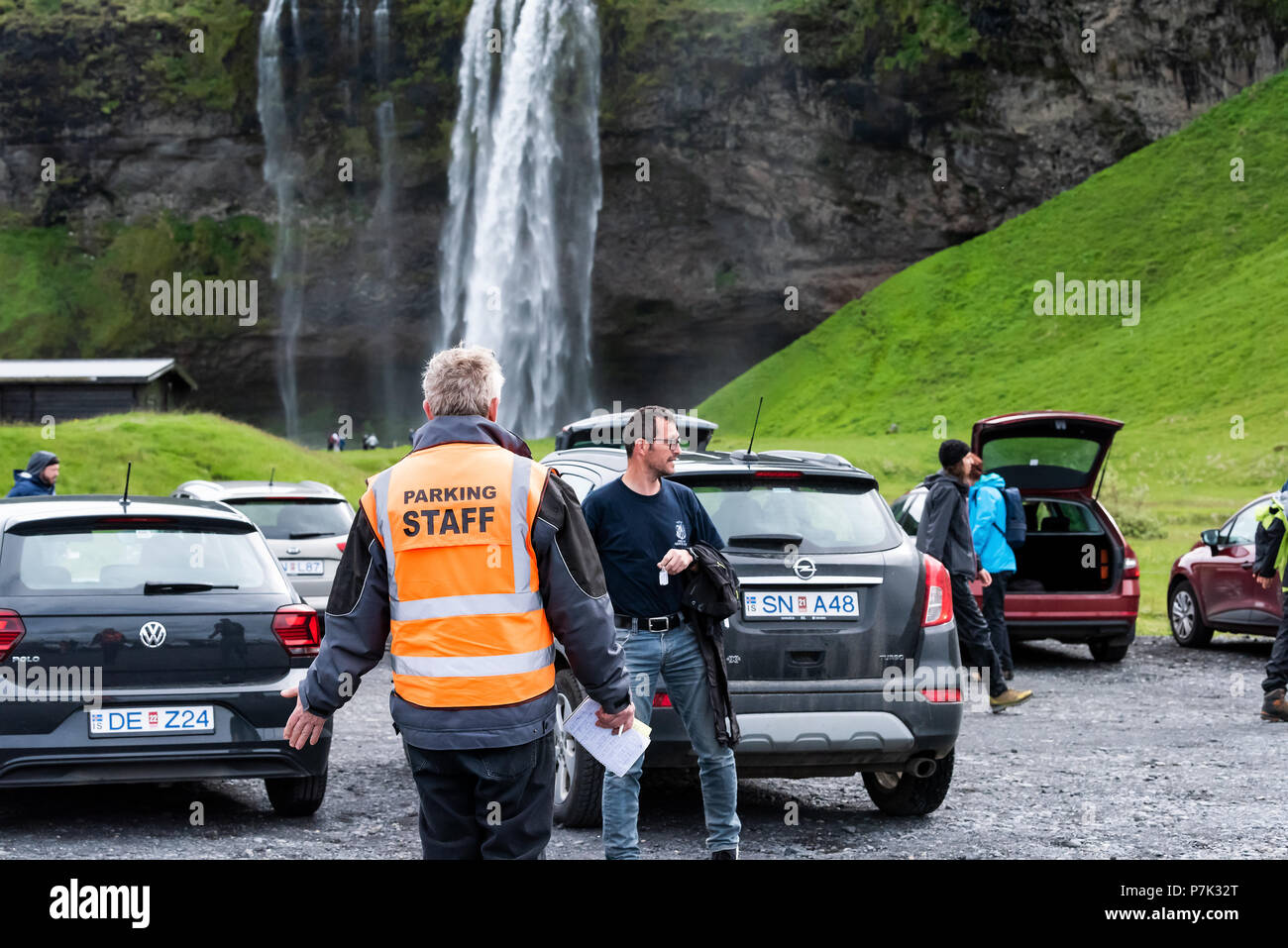 Seljalandsfoss, Iceland - June 14, 2018: Parking lot by waterfall with security guard officer writing tickets in orange vest, tourists walking, cars - Stock Image