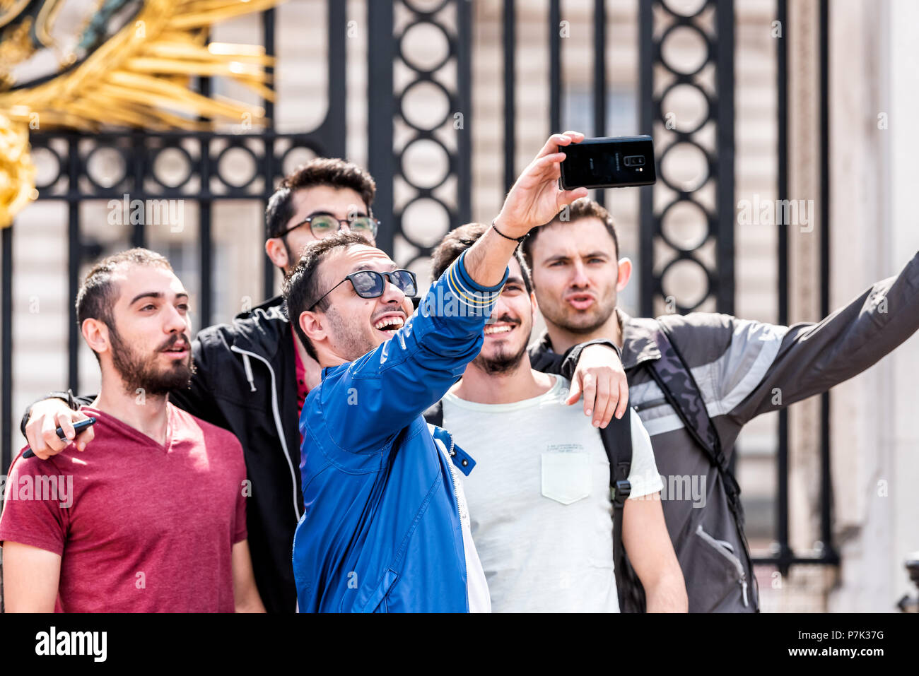 London, UK - June 21, 2018: Group of young men male faces friends standing taking happy selfie smiling and laughing in front of Buckingham Palace clos - Stock Image
