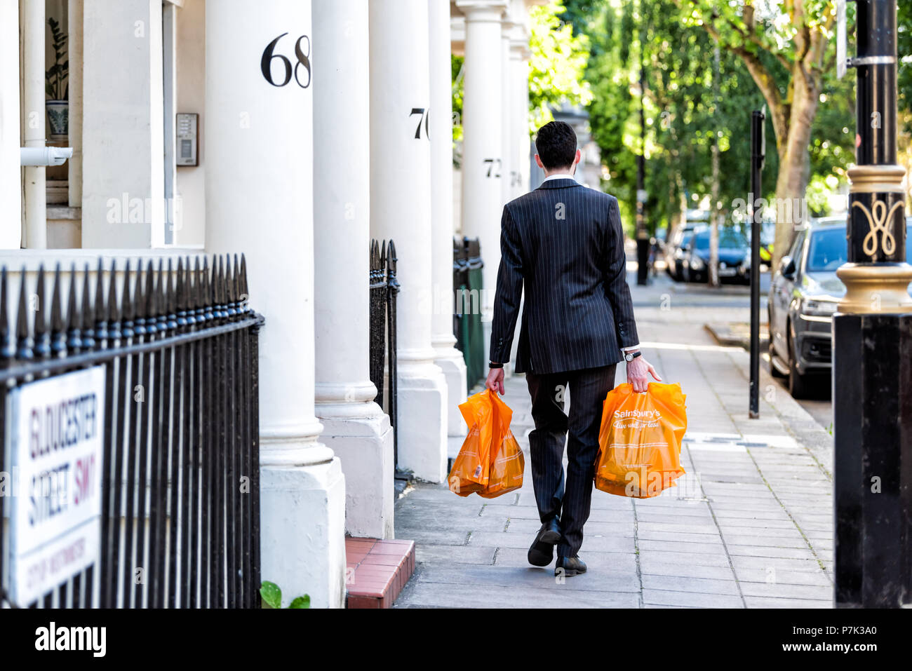 London, UK - June 22, 2018: Neighborhood district of Pimlico, Gloucester Street, businessman man carrying grocery shopping bags after work in evening  - Stock Image