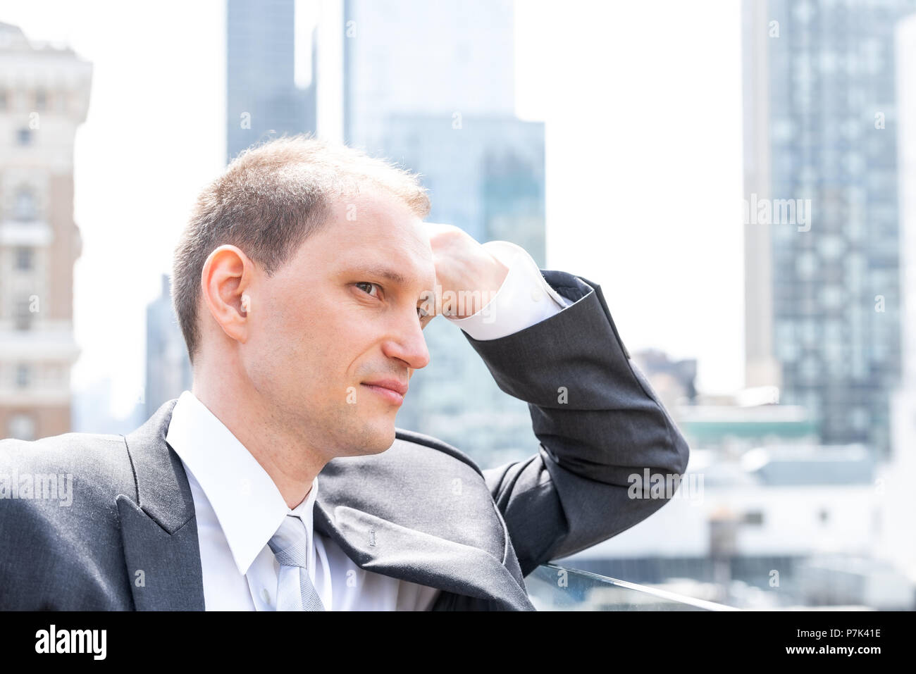 Handsome, attractive young side profile businessman closeup face portrait standing in suit, tie, looking at New York City cityscape skyline in Manhatt Stock Photo