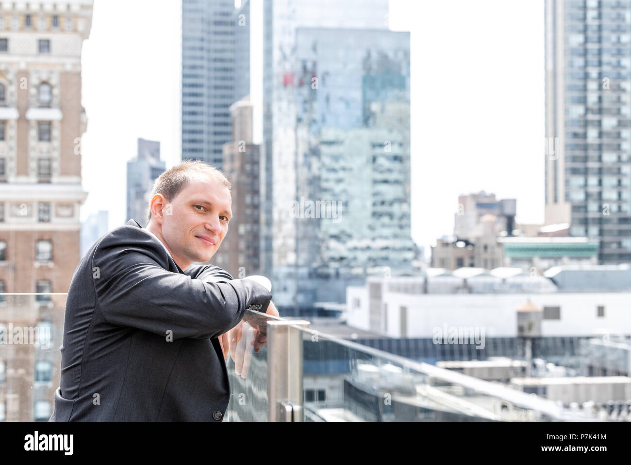 Young businessman portrait standing in suit, tie, looking at New York City cityscape skyline in Manhattan at skyscrapers rooftop happy smiling Stock Photo